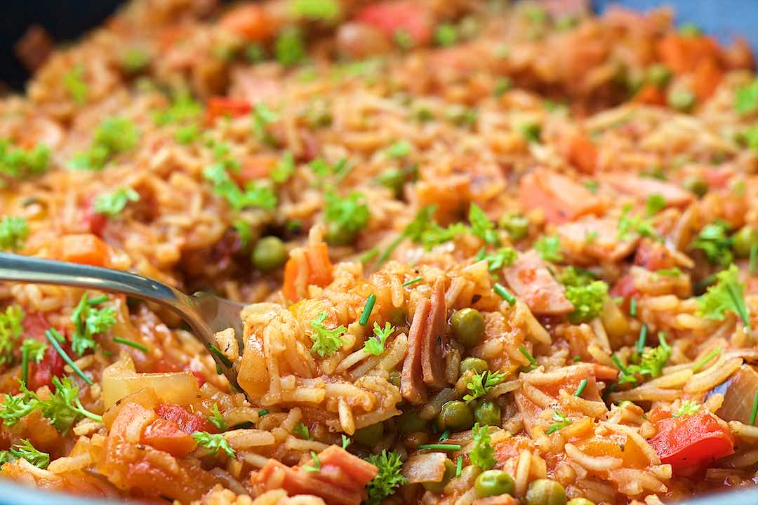 Close up view of Mexican rice with tomatoes ham peas and peppers