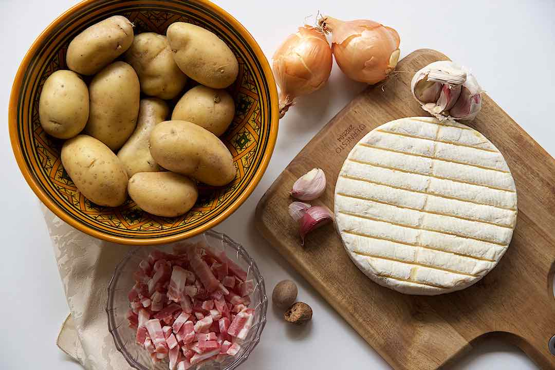 Ingredients tartiflette with potatoes, bacon, onions, garlic, reblochon cheese and nutmeg