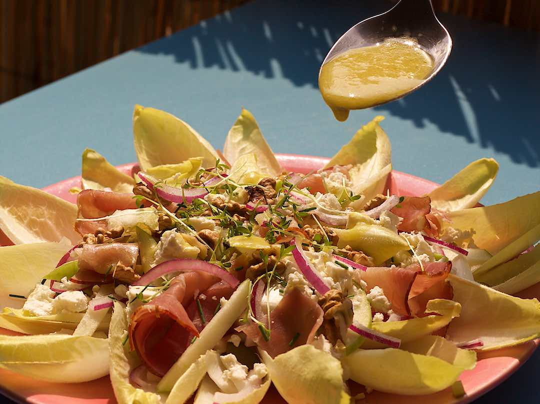 Belgian endive salad with ham apple walnut feta cheese with honey mustard dressing on a pink plate and blue table