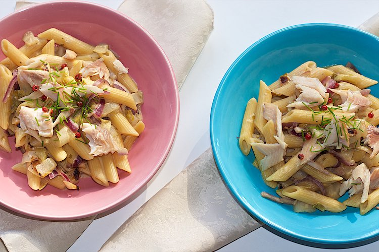 Penne pasta with smoked trout, Belgian endives, red onion, chives and pink peppercorn in a pink and blue plate