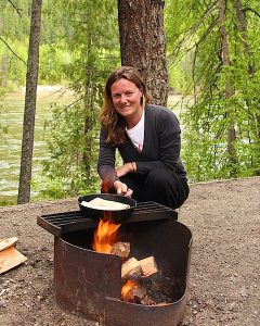 smiling woman cooking on open fire next to a river