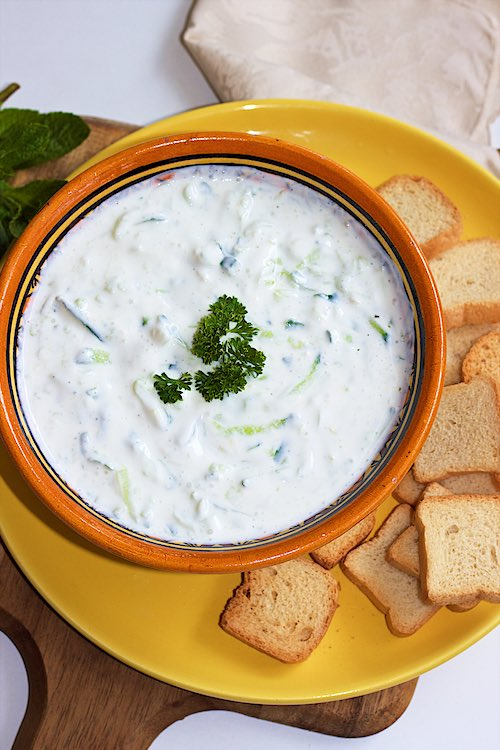 Griekse tzatziki yoghurt en komkommerdip die in een gele kom met crackers op een geel bord wordt opgediend