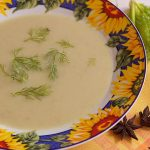 Fennel soup with zucchini and star anise in a flower plate and yellow napkin