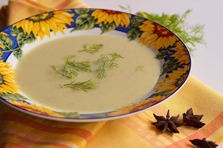 Fennel soup with zucchini and star anise in a flower plate and yellow napkin and three star anise