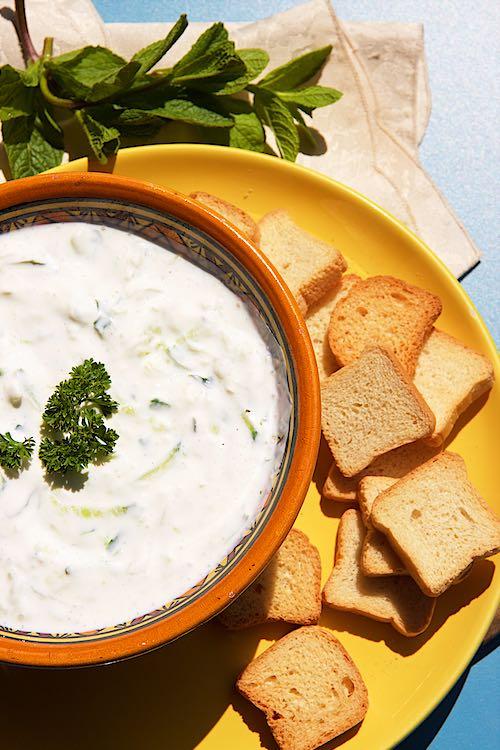Griekse tzatziki yoghurt en komkommerdip die in een gele kom met crackers op een geel bord en muntdecoratie wordt opgediend
