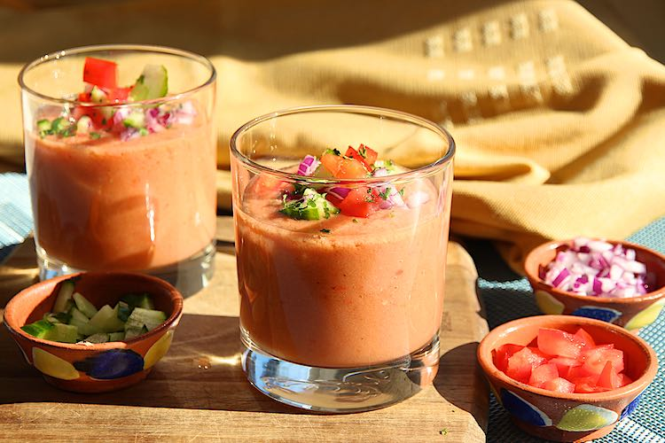 Easy Spanish gazpacho recipe with gazpacho soup in glasses with garnish in small bowls