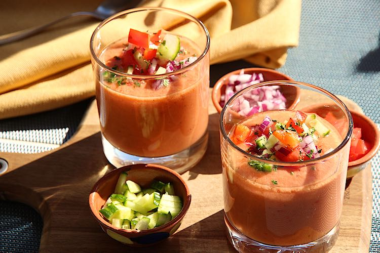 Spaanse gazpacho soep in twee glazen met garnituur op een houten snijplank
