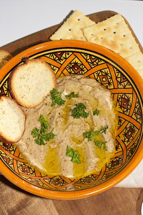 Baba ganoush roasted eggplant dip with crackers served in a yellow bowl