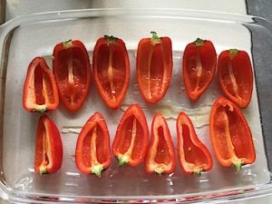 Halved mini red bell peppers in an oven dish
