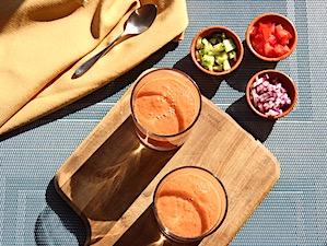 gazpacho serveren gekoeld in een glas met garnering in kleine kommen