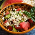 Watermelon salad with cucumber feta cheese and basil in a yellow bowl