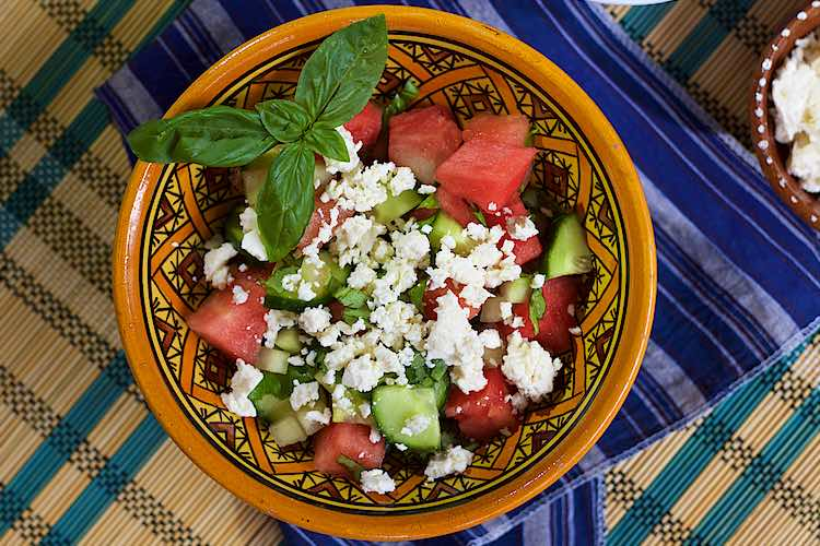 bowl of cucumber watermelon salad with feta cheese and basil sprinkled over it