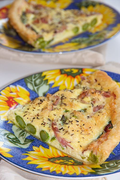 Slice of ham and asparagus quiche on a plate with sunflowers