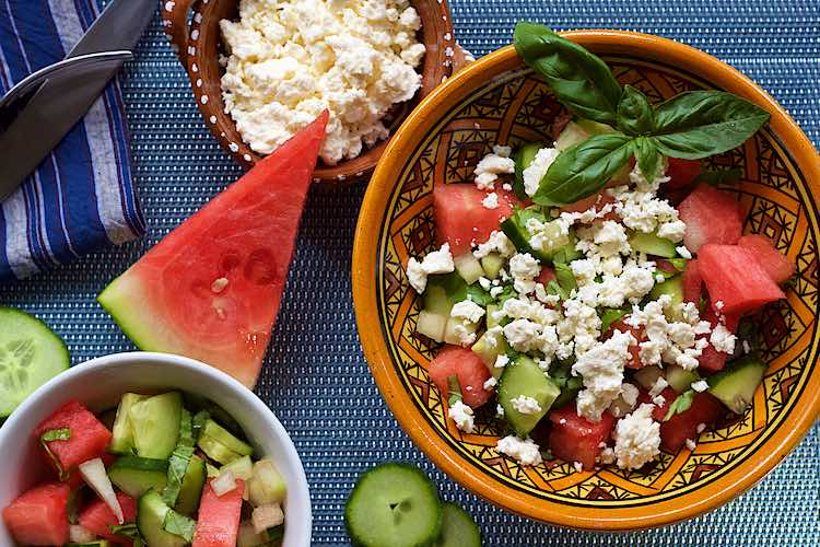 Table set with watermelon cucumber salad with feta cheese and basil in a yellow bowl on a blue table