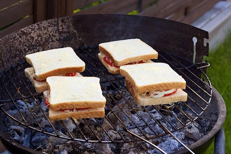 vier beboterde boterhammen met kaas en tomaat op de grill of barbecue