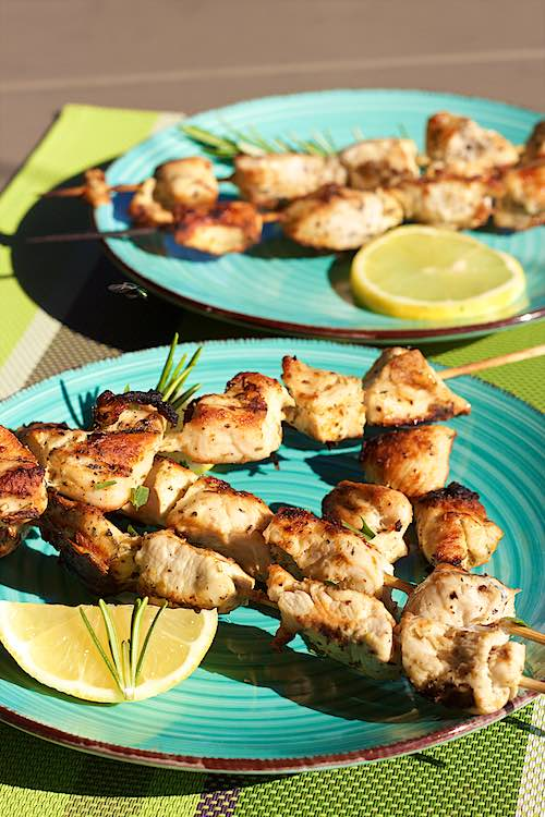 Long shot of grilled lemon herb chicken skewers on a blue plate