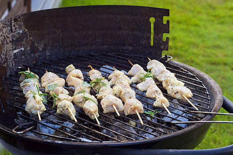 Preparing 7 chicken skewers on the bbq with coals with lemon herb marinade