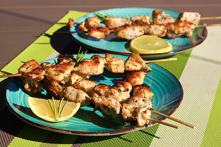 Grilled bbq lemon herb chicken kebabs with lemon slices on a blue plate