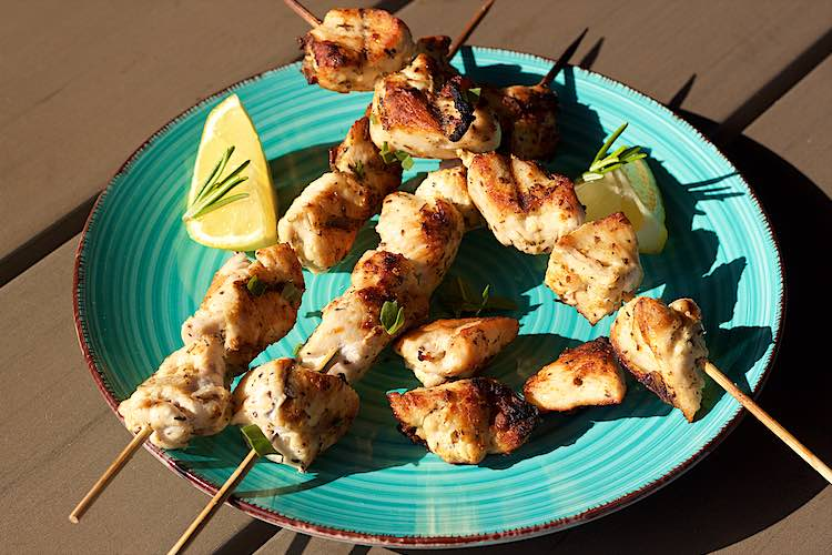 BBQ grilled chicken skewers with lemon herb marinade on a blue plate and slices of lemon