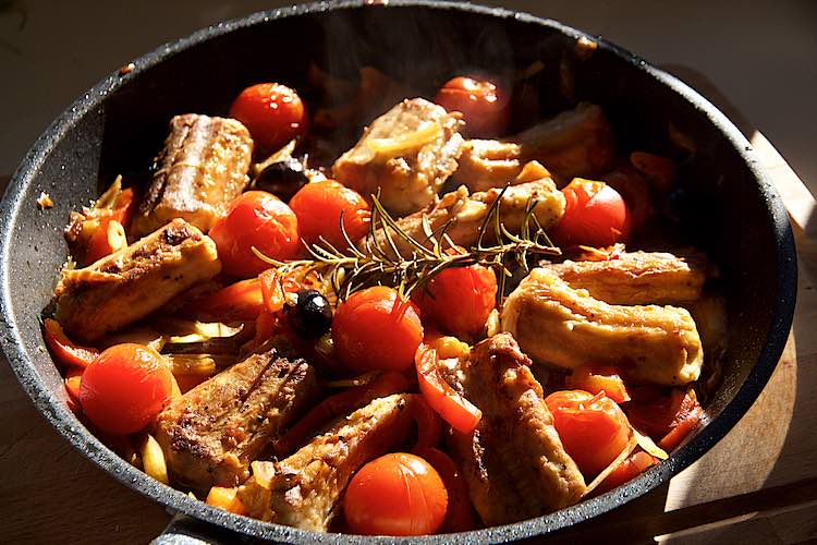 Stewed dogfish served in a pan with tomatoes, fennel and peppers