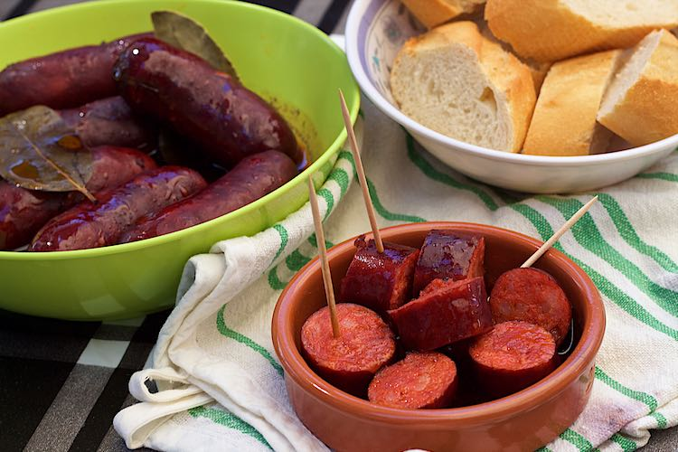 Spanish chorizo in red wine sliced in a clay pot or chorizo in vino tinto served with baguette