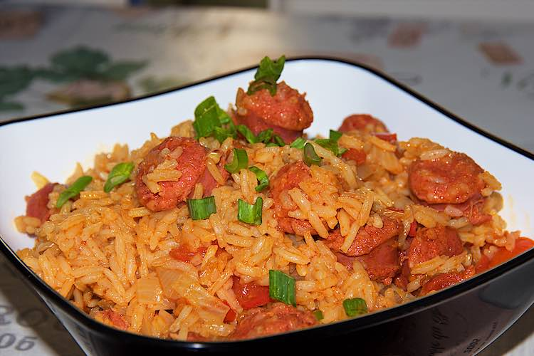 spaanse rijst met chorizo in een zwart witte kom met lente ui