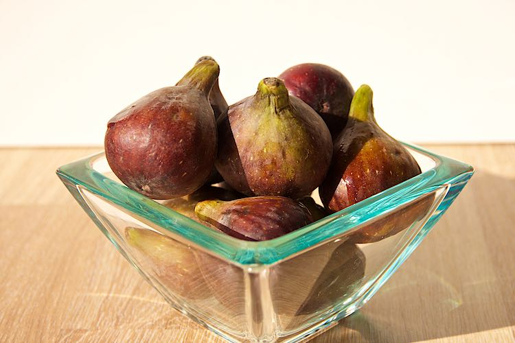 fresh figs in a glass bowl on a wooden table