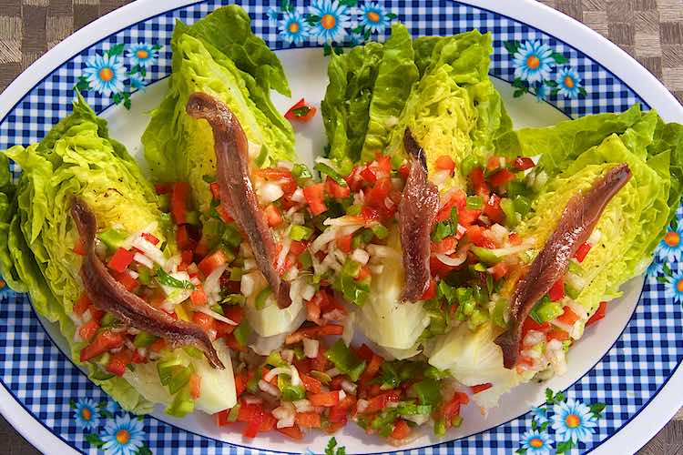 slaharten met ansjovis en paprika salsa op een geruit bord