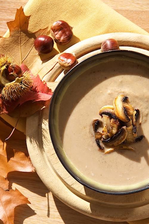 kastanjesoep met champignons op herfstbladeren