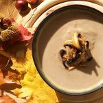 creamy chestnut mushroom soup in green bowl with colourful leaves and chestnuts