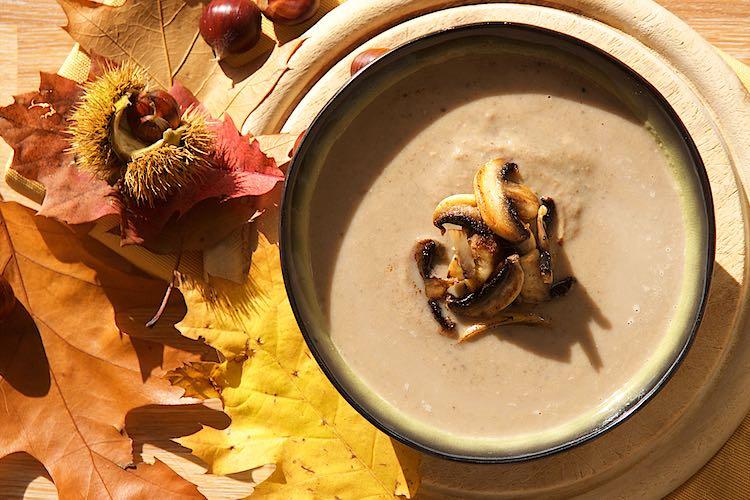 romige geroosterde kastanjesoep met champignons in een groene kom met kleurrijke bladeren en kastanjes