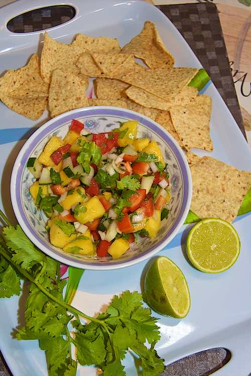 Mango salsa with lime and nachos on a white tray