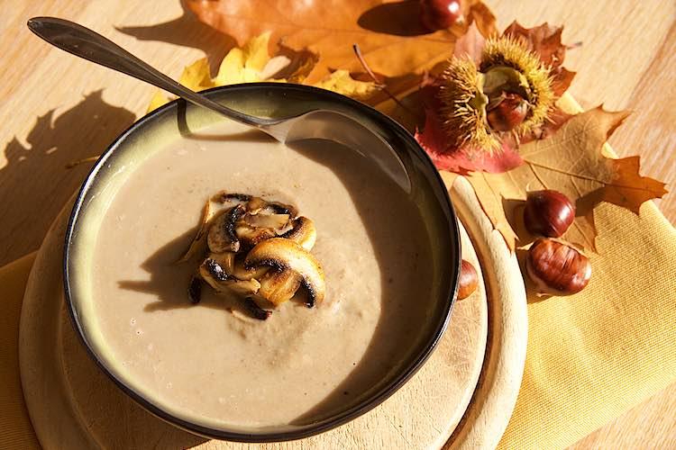 Kastanjesoep met champignons in een groene kom met lepel en herstbladeren en kastanjes