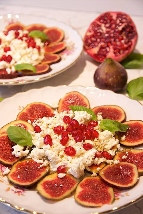 feta fig salad with pomegranate arils and basil leaves