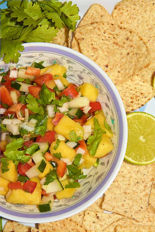 Close up easy mango salsa with cilantro, nachos and lime long shot