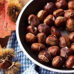 gepofte kastanje in een pan met bolsters en gekleurde herfstbladeren