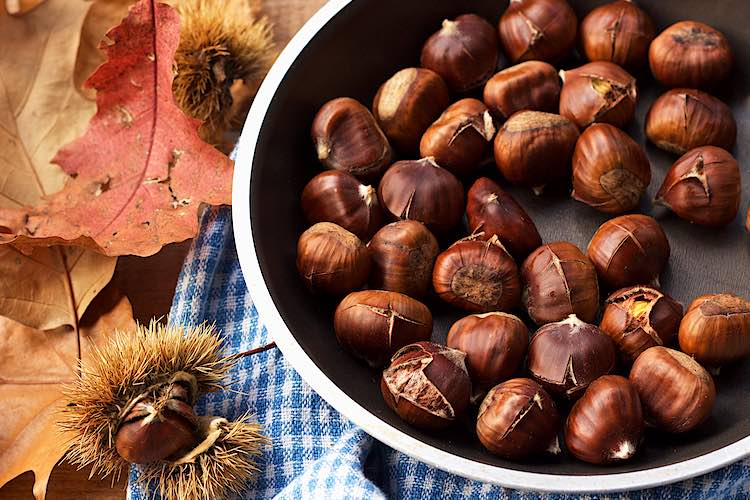 Roasted chestnuts in a pan with chestnut husks and colourful leaves