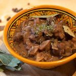wild boar stew with mushrooms served in a yellow bowl with bay leaves, cinnamon and pimenta