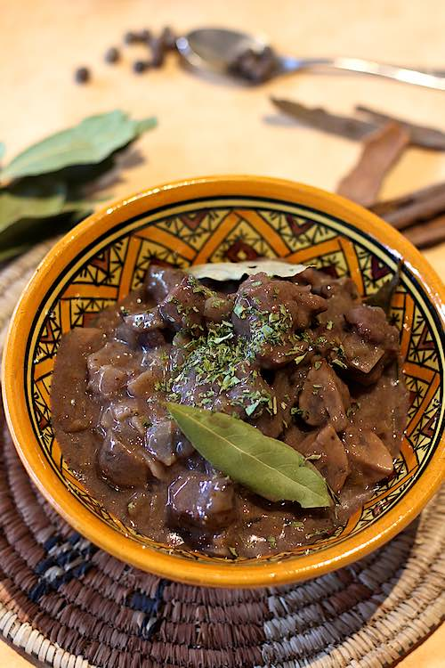 long view of wild boar casserole in a bowl with bay leaves