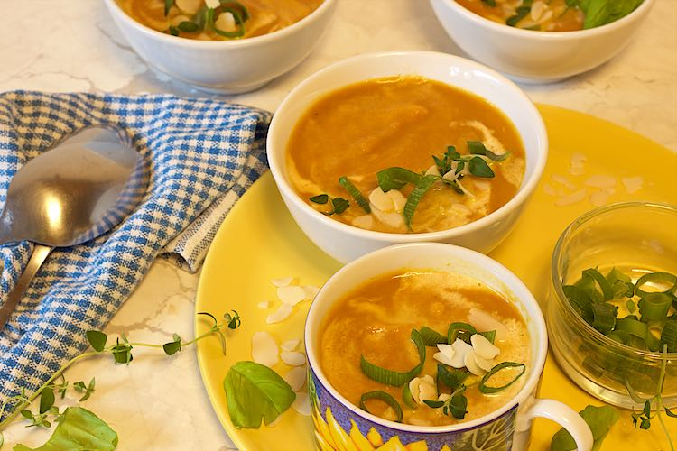 bowls of carrot ginger soup with spring onions, fresh thyme and basil leaves with a checkered towel on a yellow plate