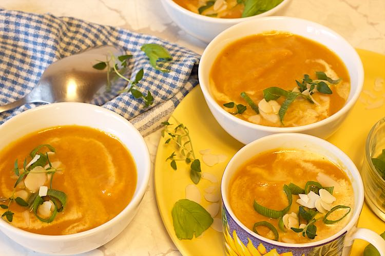 three bowls of ginger and carrot soup with almonds, thyme, basil leaves on a yellow plate and blue checkered towel