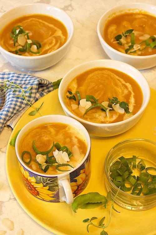 long image of 4 bowls of carrot ginger soup with toppings of almonds, spring onion, thyme and basil on a yellow plate