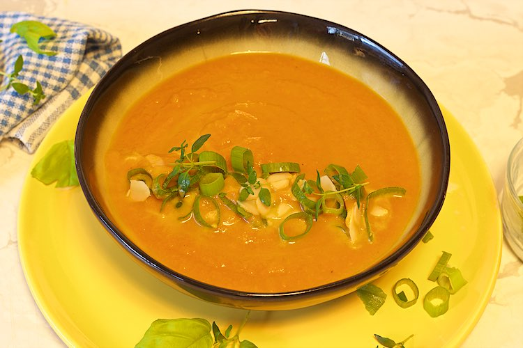 bowl of ginger carrot soup with spring onions, thyme, basil and almonds on a yellow plate