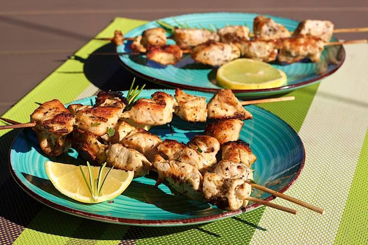 gegrilde kip brochette met citroen en kruiden met schijfjes citroen op een blauw bord