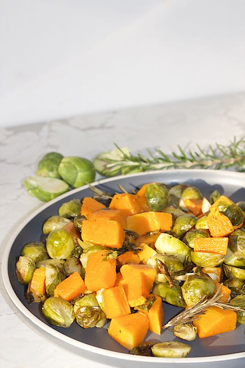 long shot of brussel sprouts and butternut on white table