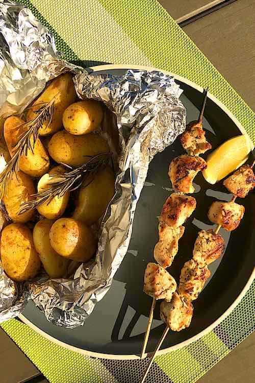 long shot of in foil bbq grilled potatoes with rosemary and chicken skewers