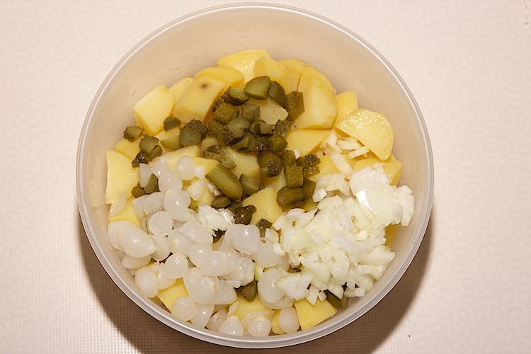 Mixing ingredients for potato salad with pickles
