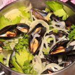 close up of steamed mussels with onions and celery
