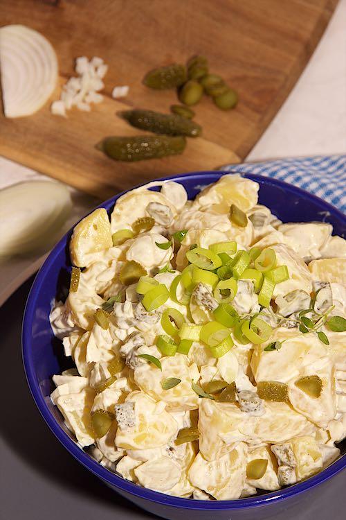 vertikale foto van aardappelsalade met zilveruitjes en augurk in een blauwe kom