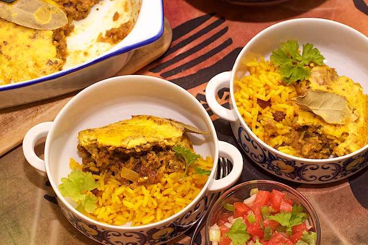 bobotie geserveerd met gele rijst in 2 kommen en tomatensalsa met ui